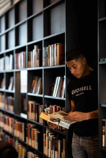 concentrated black man reading book in library