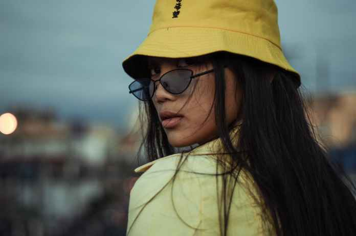 woman wears yellow bucket hat