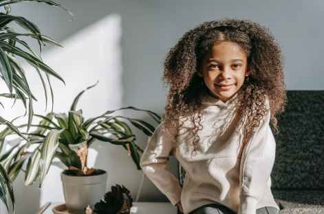 positive black girl with long curly hair sitting in living room