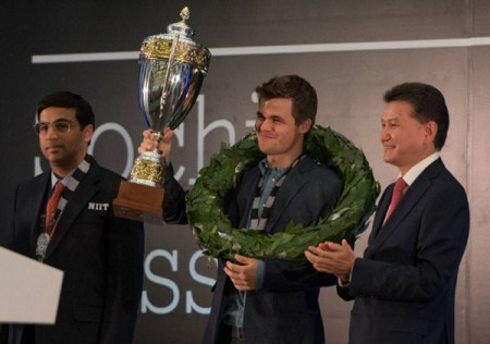 Norway's Magnus Carlsen shows his trophy at the award ceremony of the FIDE World Chess Championship Match  in Sochi, Russia, Tuesday, Nov. 25, 2014.   Magnus Carlsen won against India's former World Champion Vishwanathan Anand, left. At right is FIDE president Kirsan Ilyumzhinov. AP/PTI(AP11_26_2014_000006A)