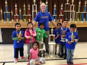 A proud head coach poses with the State Championship Kindergarten team from MSJE.