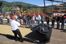 Grainpro representatives showing a portable drying bed. Photo by Daily Coffee News/Nick Brown.
