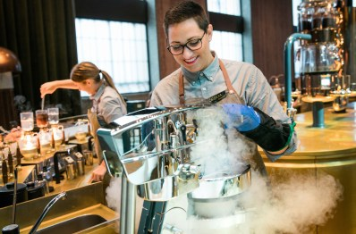Starbucks barista Cecilia Cacciatore operates a nitro ice cram maker at the Affogato Station at the Starbucks Reserve Roastery in Milan, Italy on Monday, August 03, 2018. (Joshua Trujillo, Starbucks)