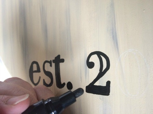 using a black paint marker to fill in letters on a farmhouse serving tray.