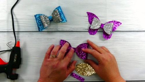 Glueing together the glitter hair bow made with a Cricut cutting machine