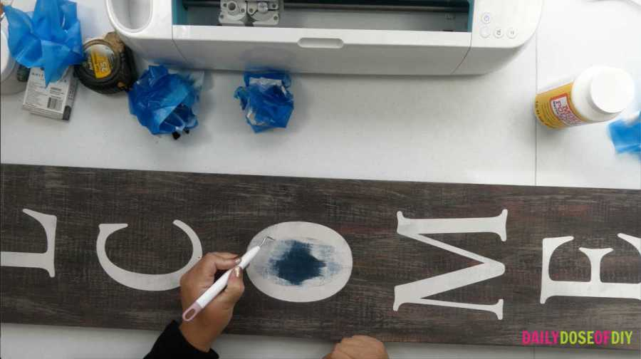 Pulling the stencil off of a vertical welcome sign using Cricut weeding tools