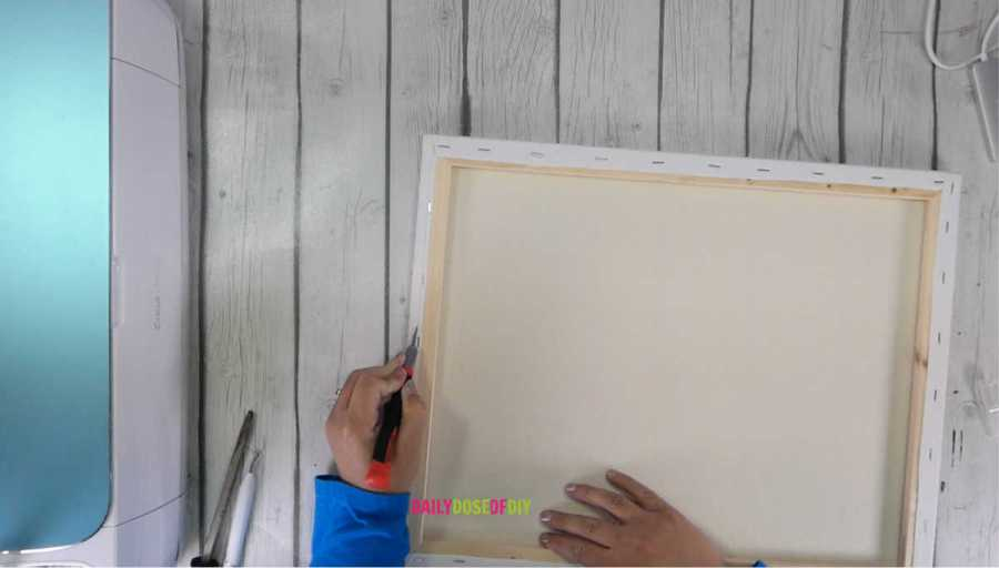 Cutting the canvas off of its frame with a utility knife