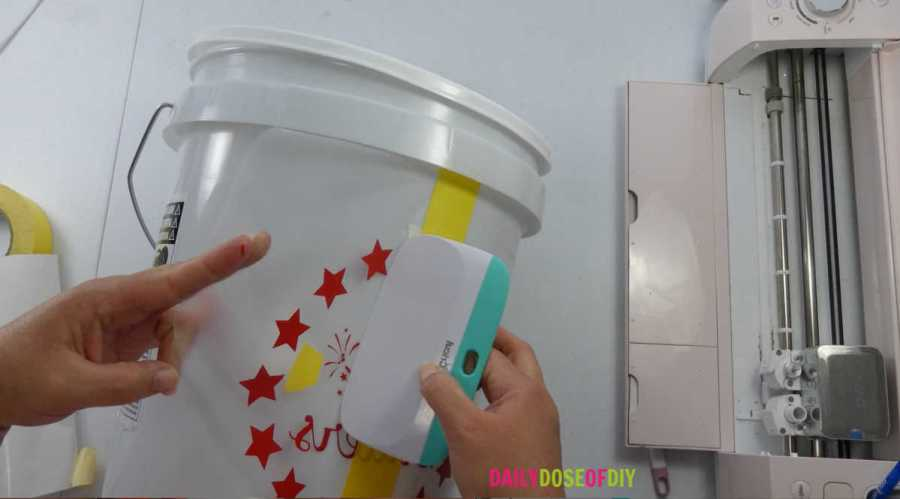 Apply the vinyl decal to your camp bucket with your Cricut scraper tool