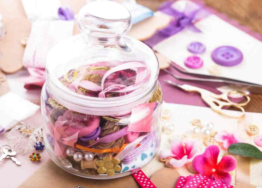 Scrapbooking craft materials organized in a glass jar
