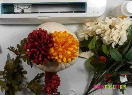 Adding faux Fall flowers to pumpkin centerpiece
