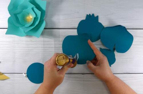gluing together the paper flower to make a paper flower display