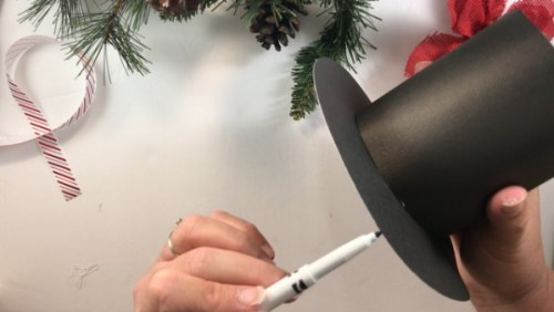 Use a black marker to cover up the white edges of your DIY snowman hat