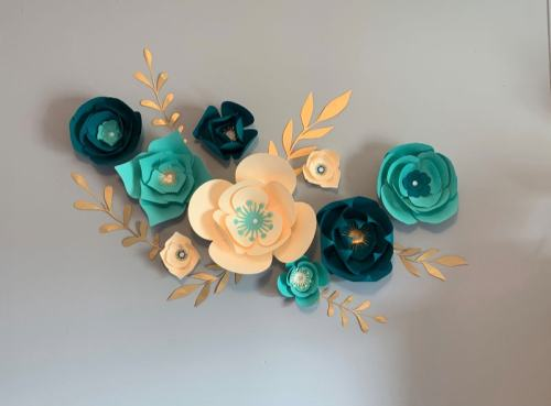Teal and cream paper flowers used for a wall backdrop