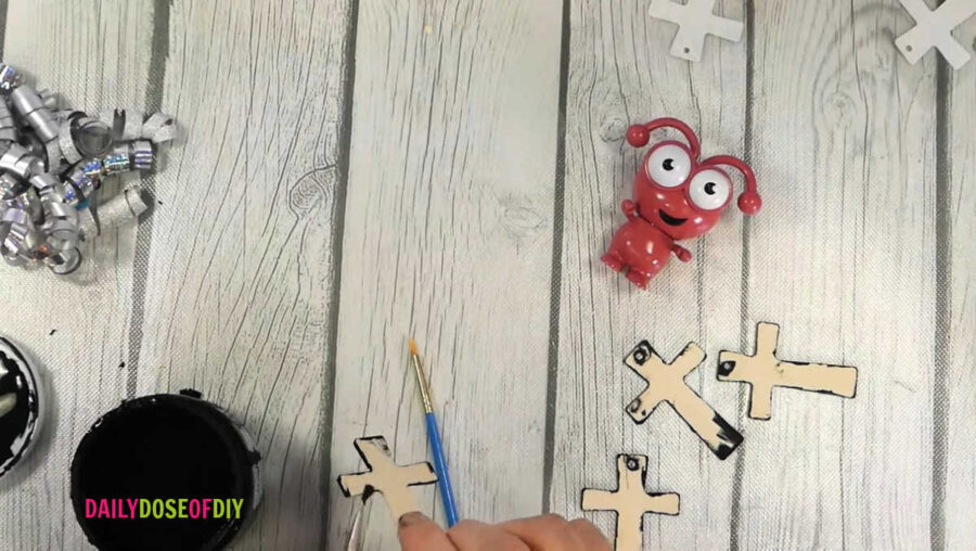painting the edges of the wooden crosses
