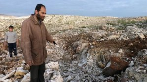 A Syrian man points at a crater where a Scud missile hit in the town of Nasiriyeh on 13 December (AFP / Herve Bar)