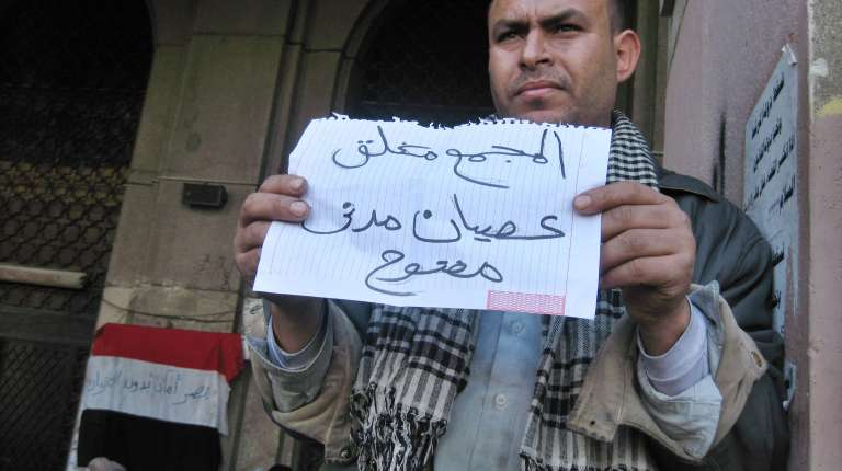 """An Egyptian Protester holds a placard reading in Arabic """"The Mugamma is closed, open civil disobedience'"""" in front of Cairo's main administrative building, as they closed its doors part of a growing campaign of civil disobedience around the country (AFP PHOTO KHALED DESOUKI)"""