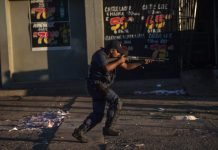 A South African riot police fires rubber bullets to prevent looting in North West Province on April 20, 2018, as protest continued for a second day in province capital of Mahikeng. South African police fired rubber bullets at protesters after President Cyril Ramaphosa cut short a foreign trip to deal with violent riots over alleged government corruption and poor public services. Shops were looted, roads were blocked and vehicles set alight in North West province in unrest that posed an early challenge for Ramaphosa, who came to power in February. At least 23 people were arrested and one man was reported to have died in sporadic violence that erupted this week in Mahikeng, the provincial capital. / AFP PHOTO / MUJAHID SAFODIEN