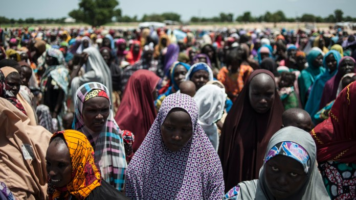 In this photo taken on women and children queuing to enter one of the UNICEF nutrition clinics at the Muna makeshift camp which houses more than 16,000 IDPs (Internally Displaced Persons) on the outskirts of Maiduguri, Borno State, northeastern Nigeria. Aid agencies have long warned about the risk of food shortages in northeast Nigeria because of the conflict, which has killed at least 20,000 since 2009 and left more than 2.6 million homeless. In July, the United Nations said nearly 250,000 children under five could suffer from severe acute malnutrition this year in Borno state alone and one in five -- some 50,000 -- could die. / AFP PHOTO / STEFAN HEUNIS
