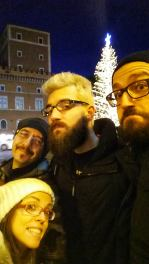 """Franz, me, Claudio and Marco smiling with Spelacchio in the background - the Christmas tree in Piazza Venezia (in Rome) that Romans renamed Spelacchio - It means """"mangy"""""""