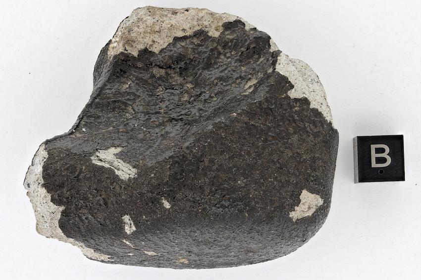 """Gros plan sur la météorite """"Tintigny"""". Le cube marqué d'un """"B"""" donne l'échelle (1 cm). © Thierry Hubin/IRSNB"""
