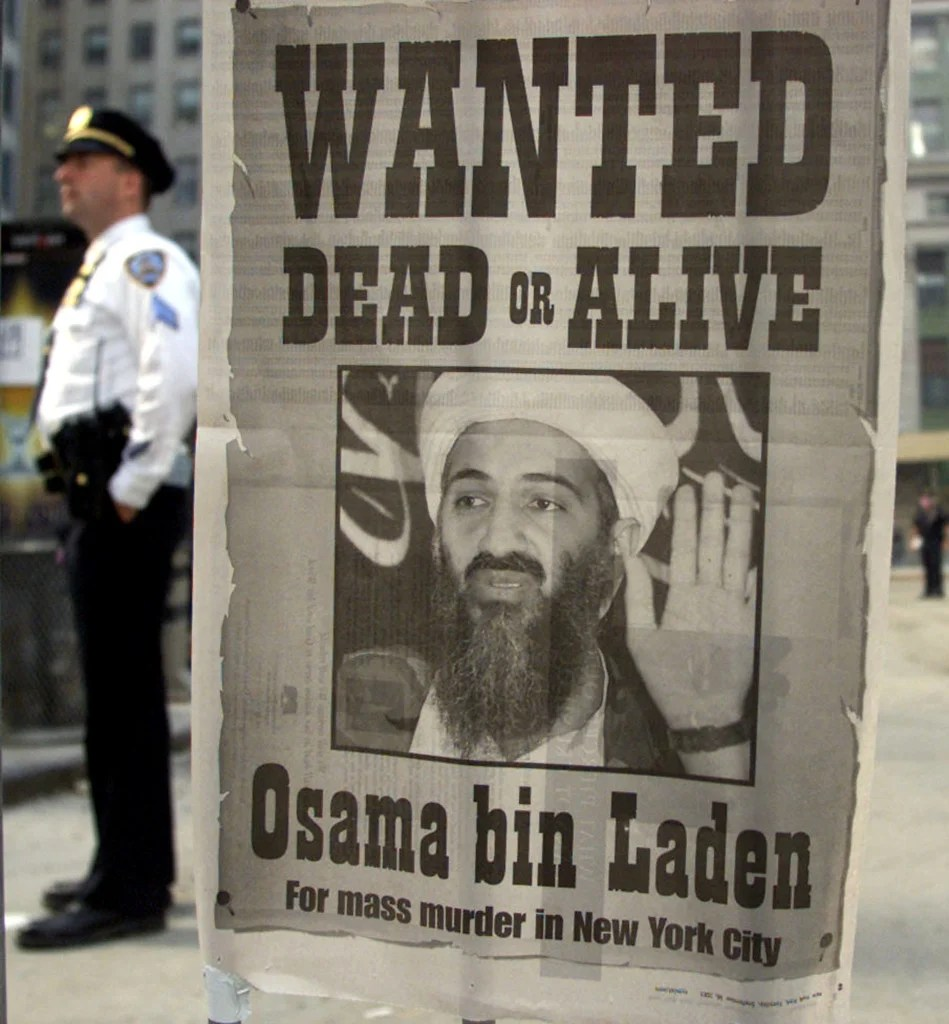 A police officer stands near a 'Wanted' poster for the Saudi-born militant Osama bin Laden in the financial district of New York, September 18, 2001. (Photo: REUTERS/Russell Boyce/Newscom)