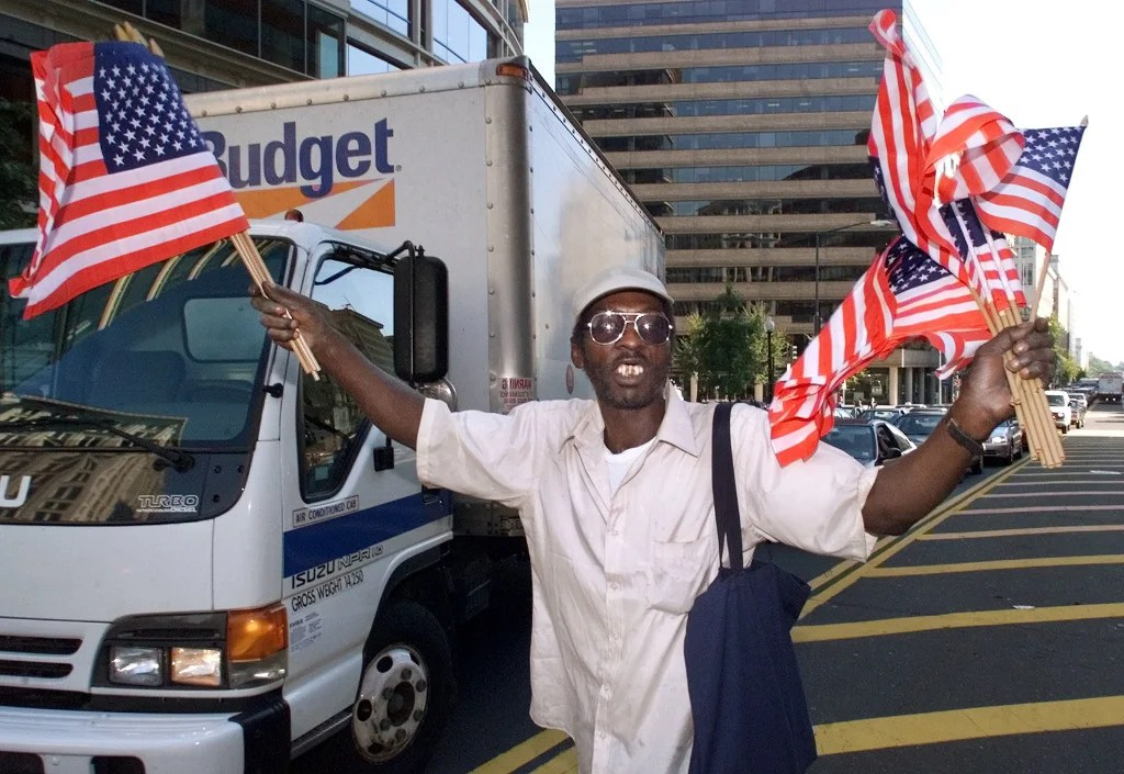 Jeremy Hodgkins hands out American flags to drivers in Washington D.C. September 13, 2001. Immediately after the attack flag sales soared in the United States -- with many stores emptying their inventory. (Photo: REUTERS/Win McNamee/Newscom)