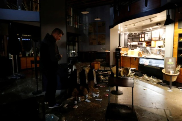 A worker surveys the damage to a vandalized Starbucks after a protest turned violent at UC Berkeley during a demonstration over Yiannopoulos in Berkeley, California. (Photo: Stephen Lam/Reuters/Newscom)