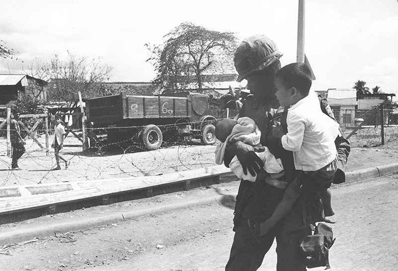 An American soldier is keeping a young boy and a newborn in his arms. In the background, a truck and other two children behind a barbed-wire fence. Saigon, 1968. (Photo: monhistorypix/Newscom)