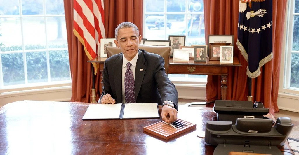 President Barack Obama signs presidential memorandum on paid leave to federal employees in the Oval Office of the White House, Jan. 15, 2015. (Photo: Olivier Douliery/ISP/Newscom)