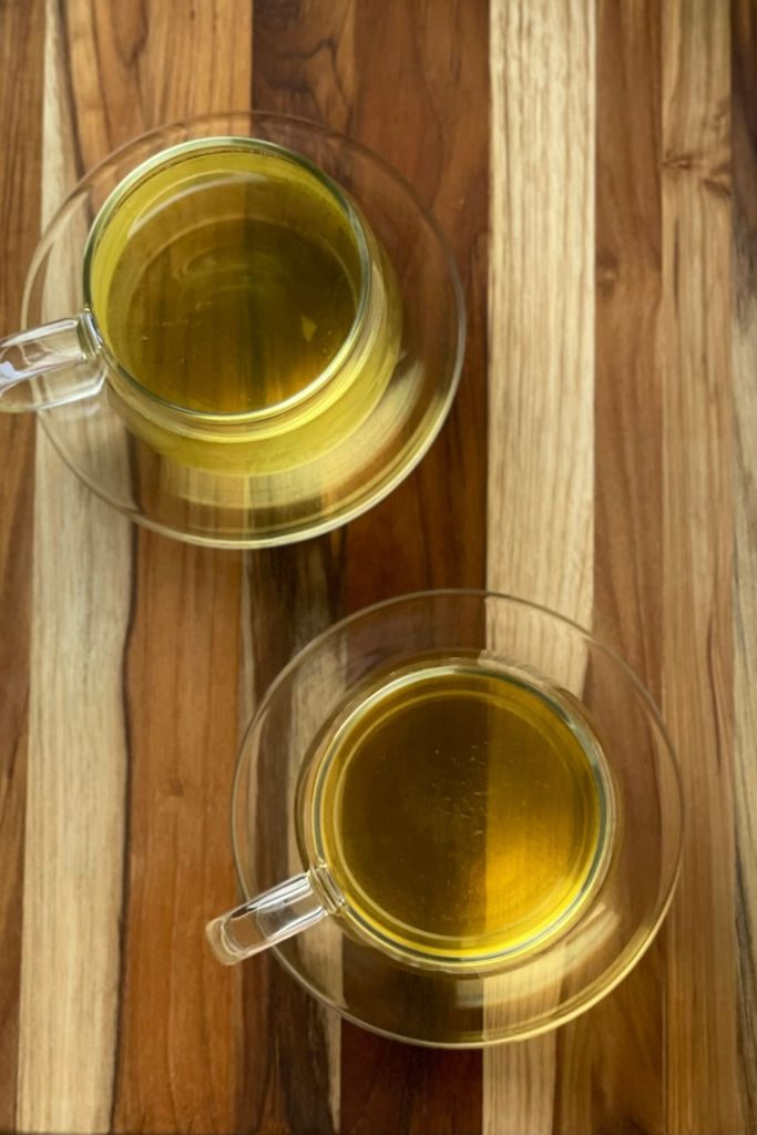 cups of jasmine tea on wooden board