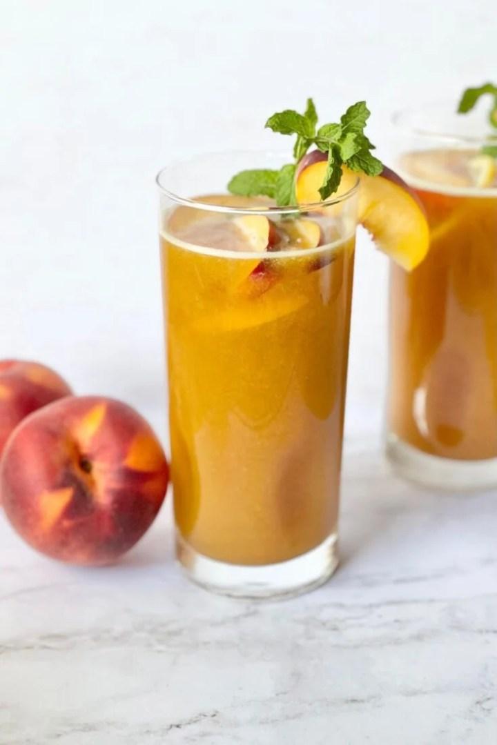peach iced tea with peaches on counter