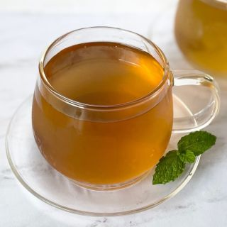 mint tea in cup with saucer and mint leaves