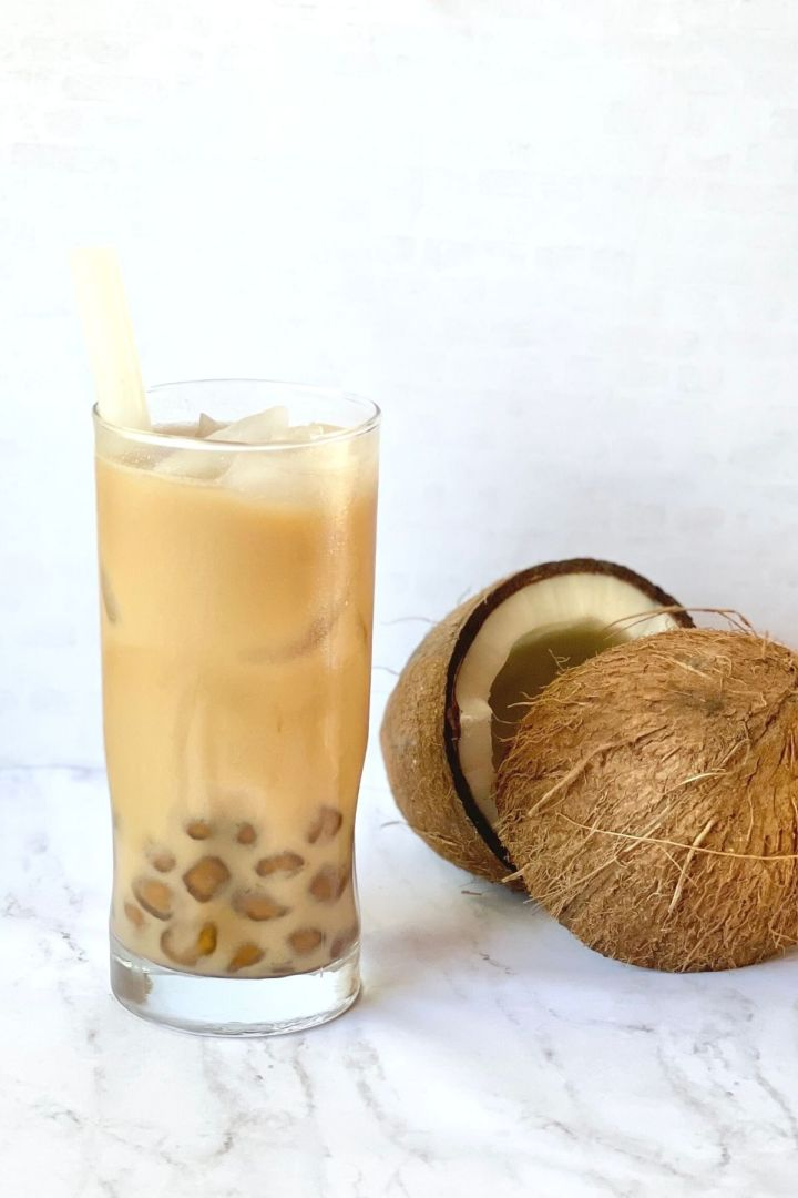 coconut milk tea with boba and two coconut halves