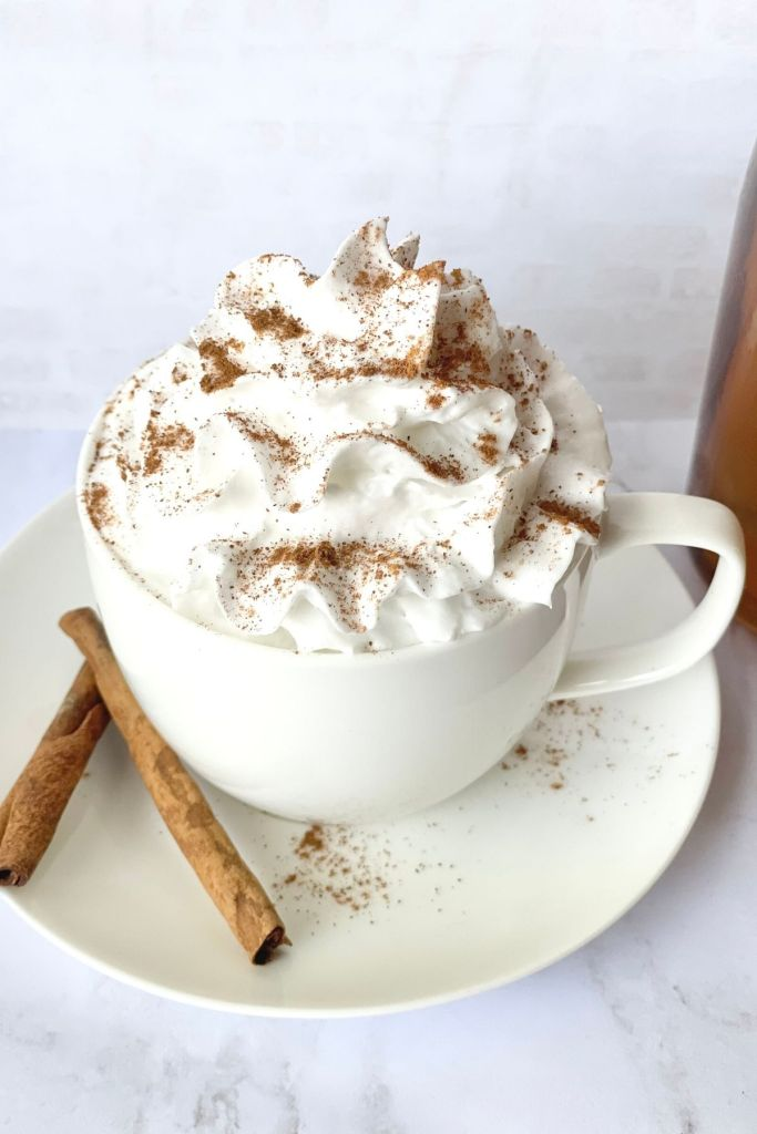 whipped cream on top of a pumpkin spice chai tea latte