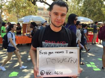 Photo courtesy of Anthony Umanzor Auspicious starts · Students held up signs at the First-Generation Student Union's booth at the involvement fair earlier this semester.