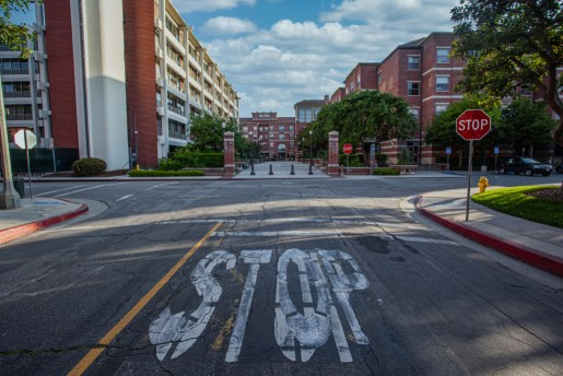 An overpainted white 'STOP' lays in the cracked and worn road leading into Parkside Apartments and Parkside dining hall. A vibrant red stop sign to the side of the road reiterates the white lettering and a white cloud scatter blue sky overlooks the buildings.