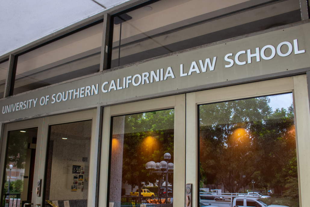 "A picture of gold lettering with ""University of Southern California School of Law"" is displayed above a glass window entrance. In the background of the entrance is a set of orange lights and a large tree and various vehicles are reflected in the windowed doors."