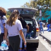 Volunteers take gallons of water out of a van parked by Skid Row.