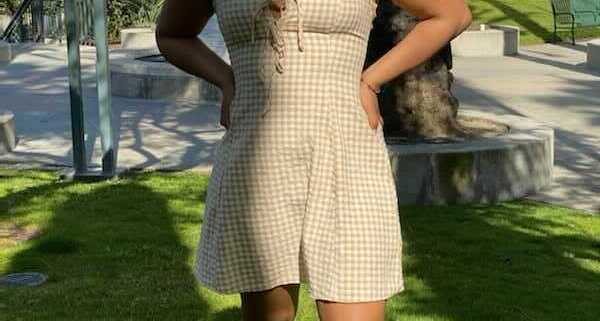 A photo of Jaya Hinton, smiling towards the camera with her hands on her hips. She wears a yellow and white checkered dress with an off-white building and palm trees in the background.