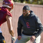 USC Trojans wide receiver coach Keary Colbert in a drill with a player in a red jersey at practice.