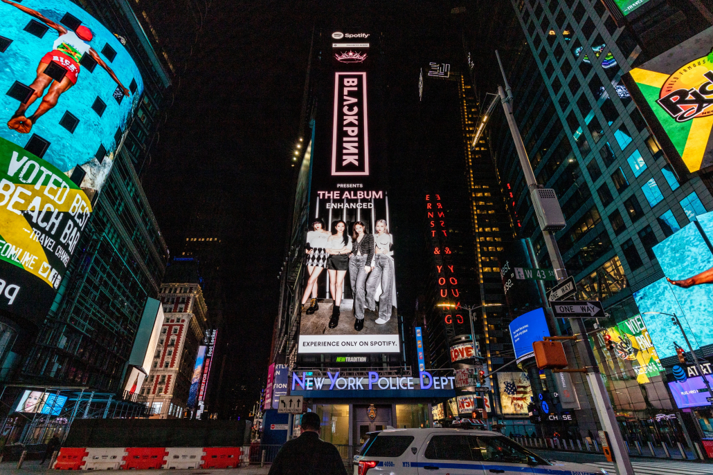 """A photo of Times Square in New York City, featuring bright lights and a Spotify ad for BLACKPINK's new album, """"The Album."""""""