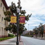 "A sidewalk on campus with banners on lampposts telling people to ""Mask up"". On the left is the yellow building of the school of cinematic arts and next to the road is the red building of the uytengsu aquatic center"