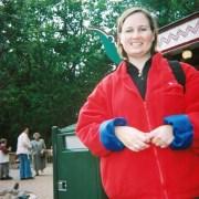 Jennifer Van Loy wearing a red fleece standing in front of trees