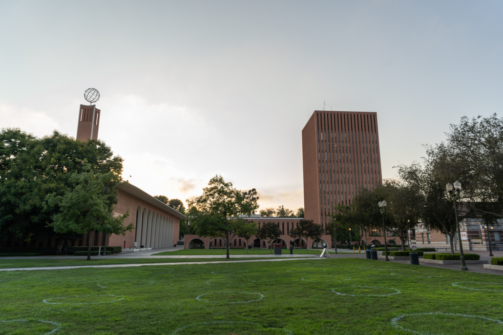 A green grass lawn is shown in front of two red brick buildings, including the Social Sciences Building which has a metal globe on top of a tower.