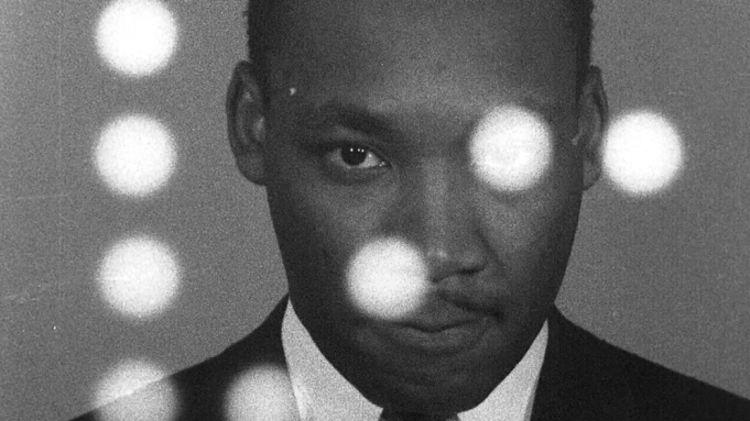MLK standing in front of white circles.