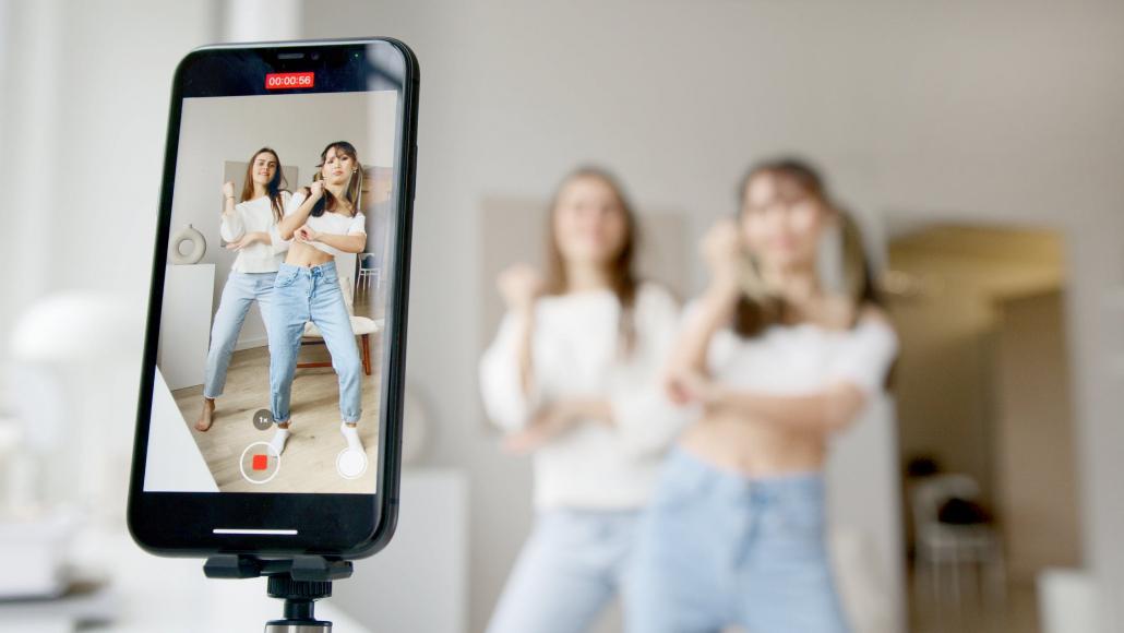 Phone filming two women dancing.