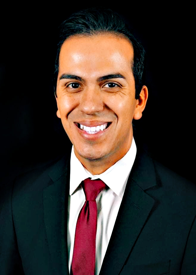 A picture shows  a headshot of James Martinez smiling in a suit with a red tie.