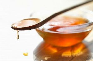 A spoon full of honey sits on a bowl full of honey