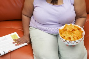 Woman sitting on couch with magazine and crisps, mid section