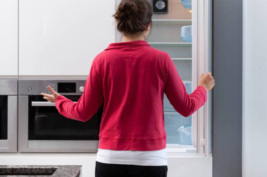 woman opening empty fridge